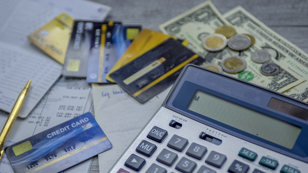 CGI Advantage Collections desk with calculator, cash and cards