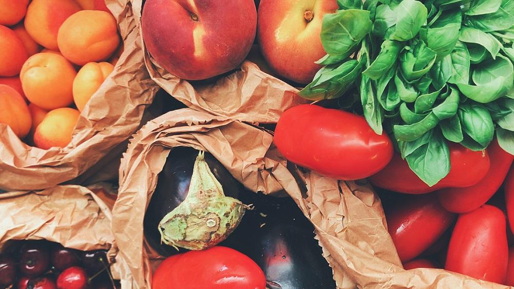Färgglada grönsaker i papperspåsar