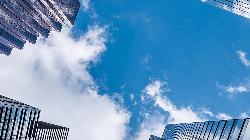 Street view of clouds above high-rising buildings in a city