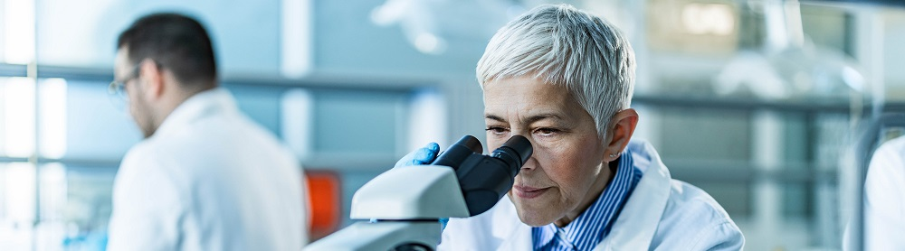 Scientist in a lab looking through a microscope to create change.