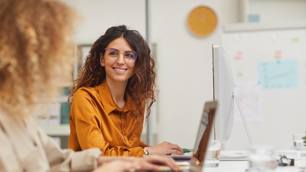 Kvinna med glasögon tittar leende på en kollega medan de jobbar tillsammans vid sina laptops