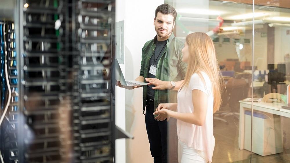 Manlig och kvinnlig kollega står vid en datacentral på ett kontor
