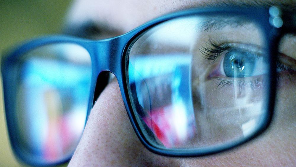 Närbild på glasögon och en person som läser på en skärm
