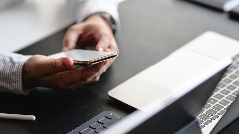 En person som läser på sin mobiltelefon framför sin uppfällda laptop och Mac