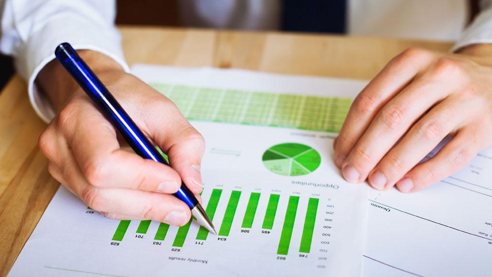 Närbild på två händer som skriver på ett papper fyllt av gröna staplar och cirkeldiagram