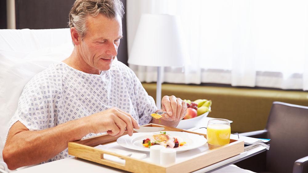 Manlig-patient-intar-måltid-i-sjukhussäng