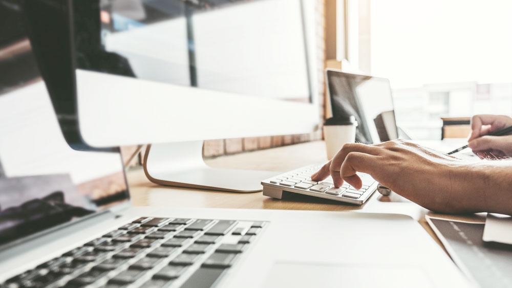 une main en train d'écrire sur un clavier avec un ordinateur