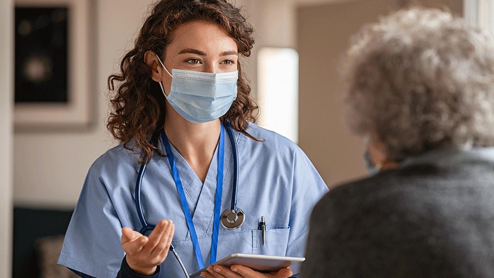 Kvinnlig läkare med munskydd samtalar med en äldre kvinnlig patient