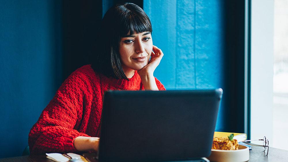Kvinna med röd tröja sitter och läser på sin laptop med hakan vilandes mot ena handen