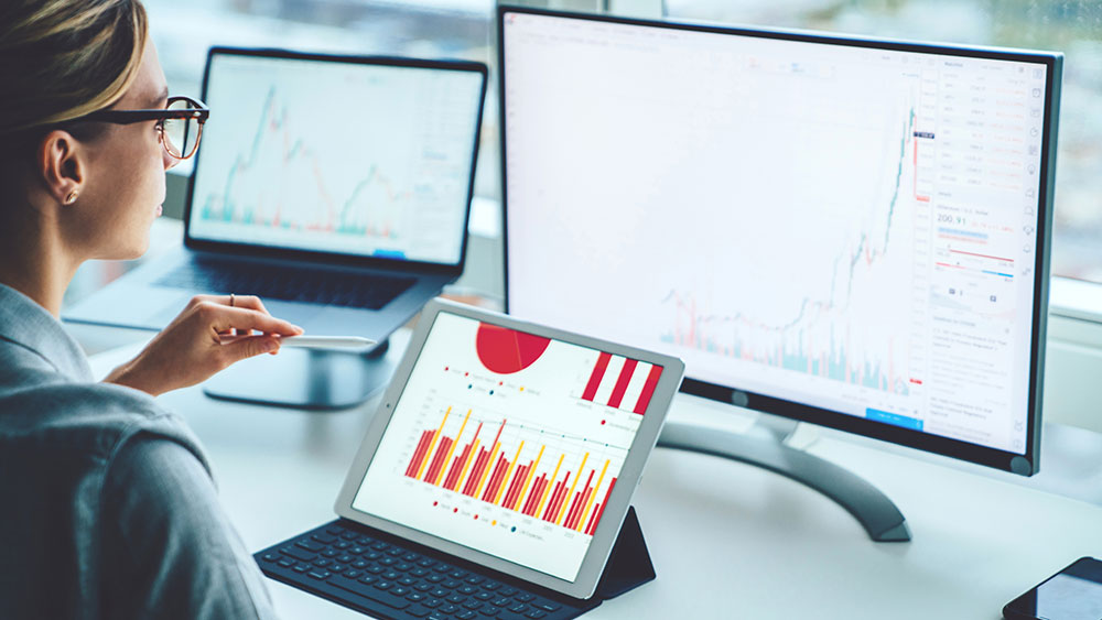 Business person viewing banking trade data on multiple screens