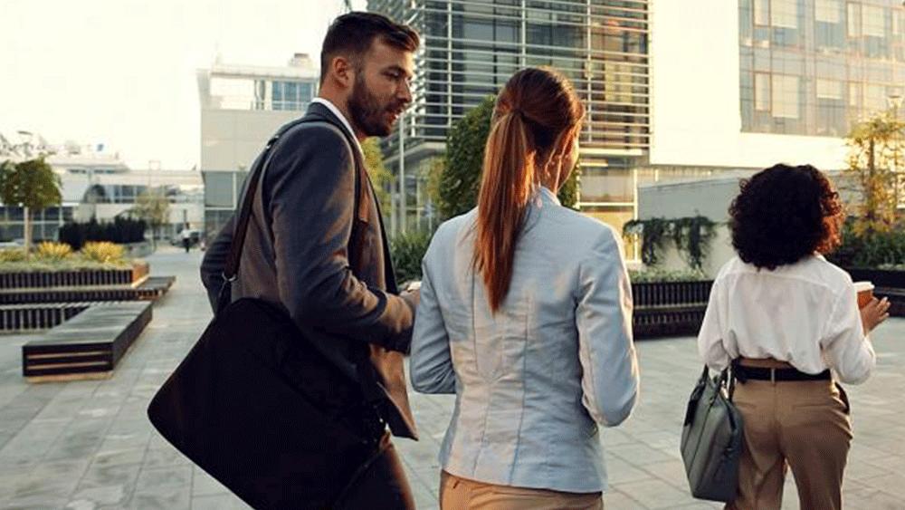 three consultants in officewear walking outside