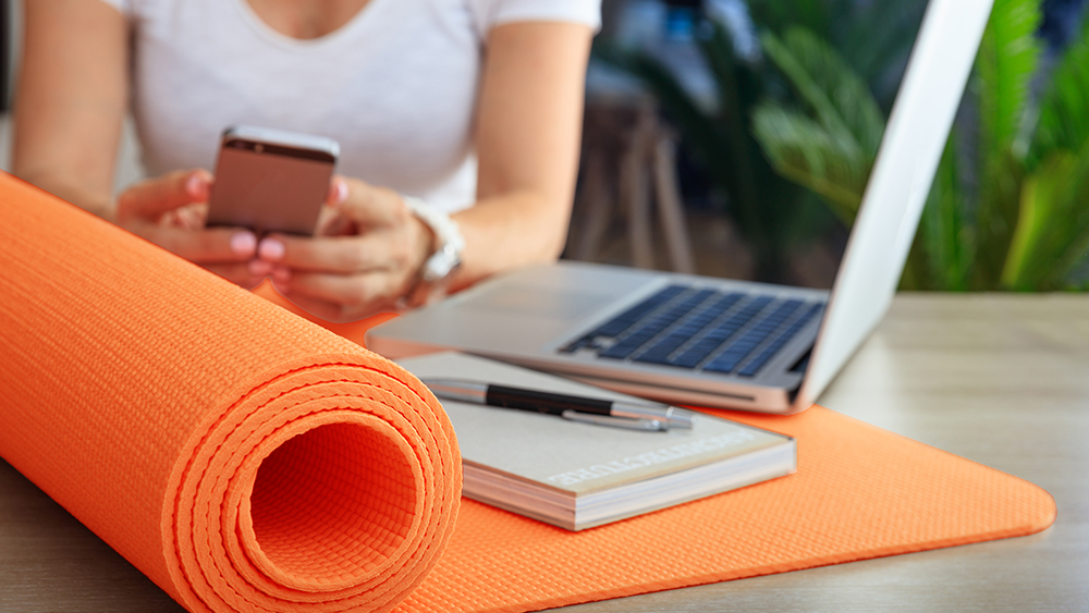 Woman sat at a desk with a laptop, mobile phone, notepad and yoga mat