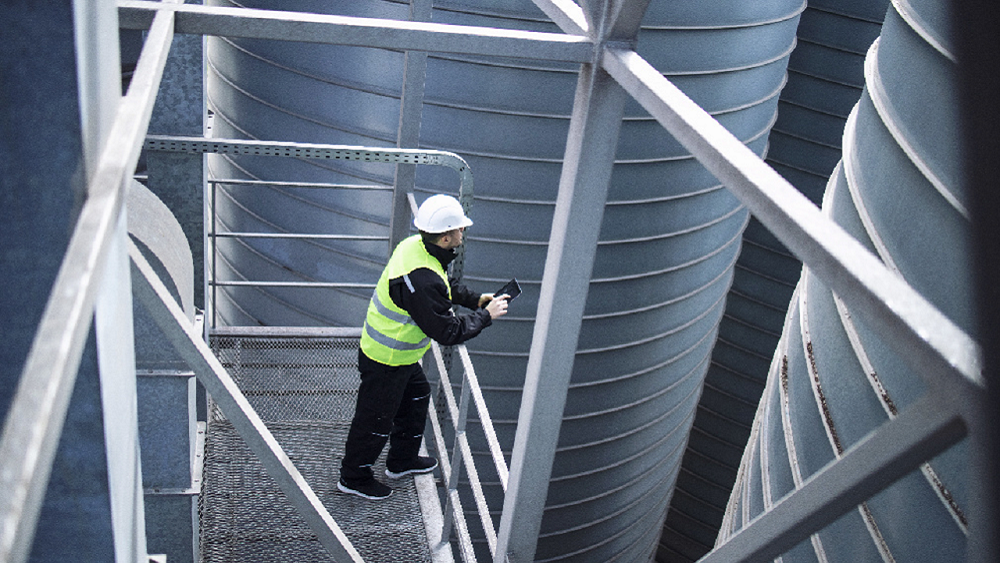 Worker in safety gear on high rise scaffolding