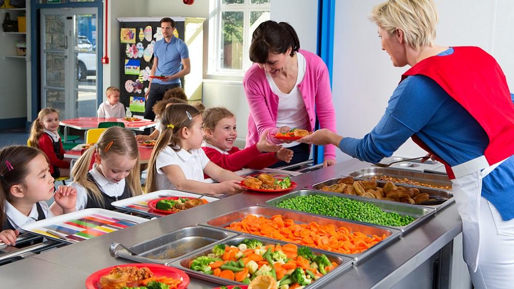 Kvinna i matbespisning på skola delar ut mat till skolelever och lärare
