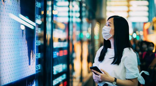 woman in a medical facemask looking at figures ona digital display board