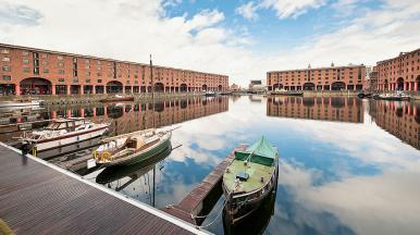 three boats at Albert Docks in Liverpool. The red buildings and cloudy sky are reflected in…