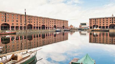 three boats at Albert Docks in Liverpool. The red buildings and cloudy sky are reflected in the water.