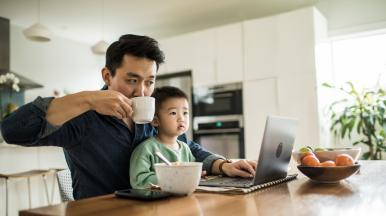 father looks at computer screen with son preventing collections during hardship times