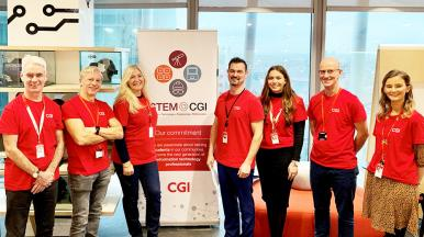 CGI Volunteers standing in front of a STEM Camp banner