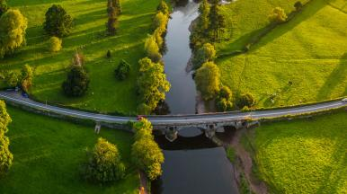 Drone view of a river cutting across a green countryside landscape