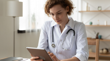 female health clinician in office with tablet