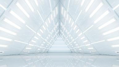 Inside of futuristic white building looking into a tunnel shaped like a triangle