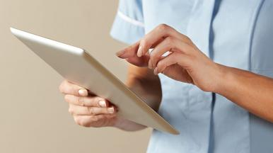 nurse looking at tablet device