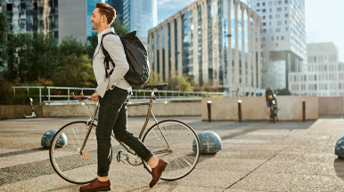 Person walking alongside bicycle in cityscape