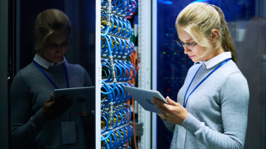 - woman in server room looking at a tablet device