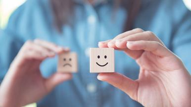Person holding two wooden dice, one with a smiley face and one with a sad face showing sentiment