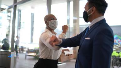 Colleagues elbow bumping in masks as they discuss CGI ROSO
