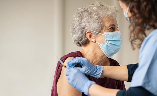doctor giving vaccine to senior woman
