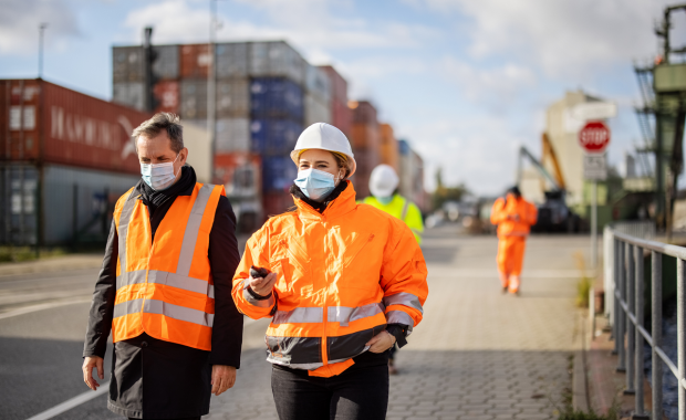 Masked workers walking on shipping docks