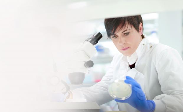 healthcare worker at microscope