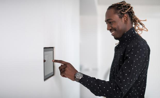 Man adjusting the temperature at home using a smart meter monitor against the wall