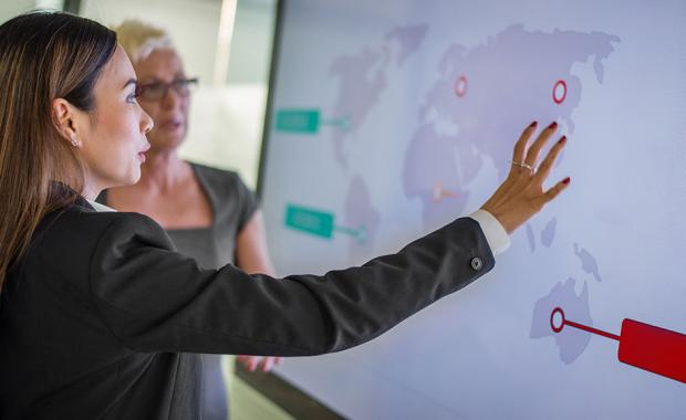 businesswoman pointing to global delivery network map