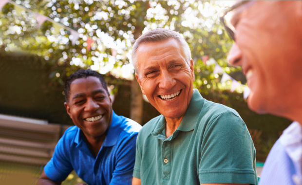 Three men sat smiling and looking content in an outdoor setting