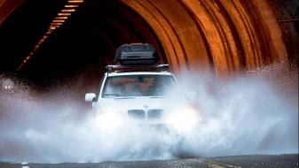 white passenger car driving through a flood at the exit of a tunnel