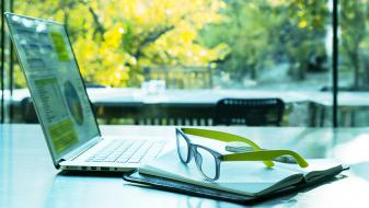 An open laptop with graphs on screen, a note pad and pair of green glasses on a table facing a sunny garden.
