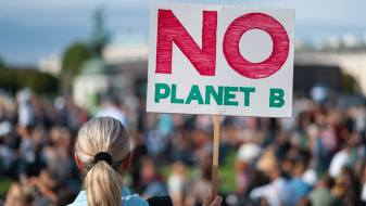 Woman seen from the back holding a No Planet B placard