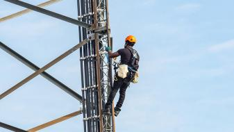 Workman doing maintenance on energy distribution tower