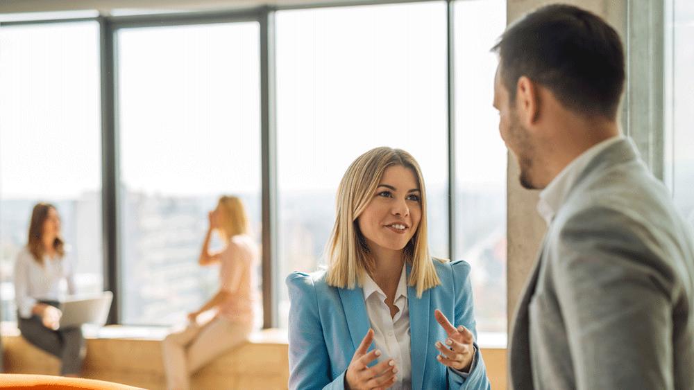 Ung kvinnlig och manlig kollega står och samtalar i en öppen yta på kontoret medan två kollegor syns sittande i bakgrunden