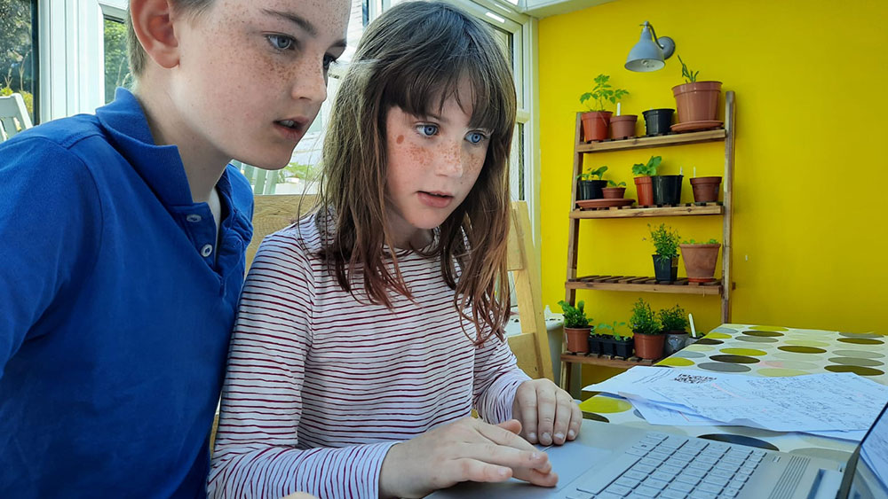 Children working on STEM activities on a laptop computer from home