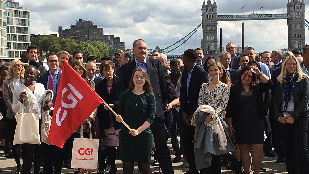 CGI Members participating in Walk Around the World in front of Tower Bridge with a red CGI flag