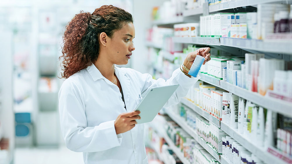 Pharmacist selecting patient medication from a shelf in a pharmacy.